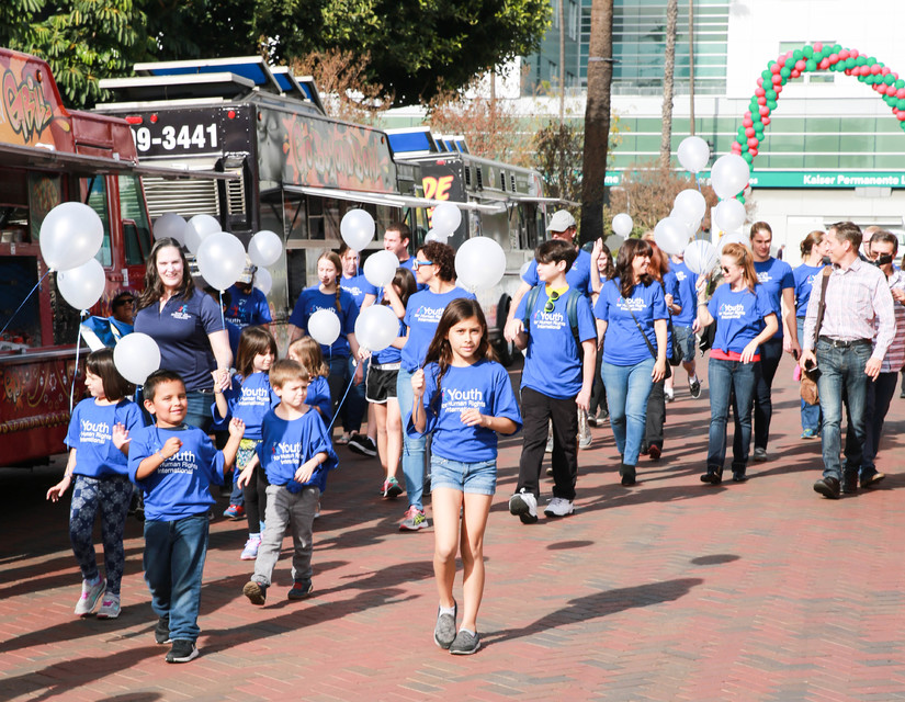 Youth walk with white balloons to spread the message of Human Rights